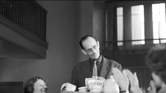 Das  8. März 1964 für eine Illustrierte gestellte Foto zeigt einen Mann mit Schürze, der einer Gruppe applaudierender Frauen eine Tablett mit Kaffeegeschirr serviert.