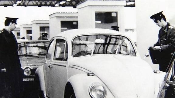 Zollbeamte kontrollieren einen VW Käfer bei der Einreise in die DDR