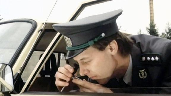 Zöllner kontrolliert mit Spezialgerät ob sich hinter der Türverkleidung eines Wartburgs Schmuggelware befindet