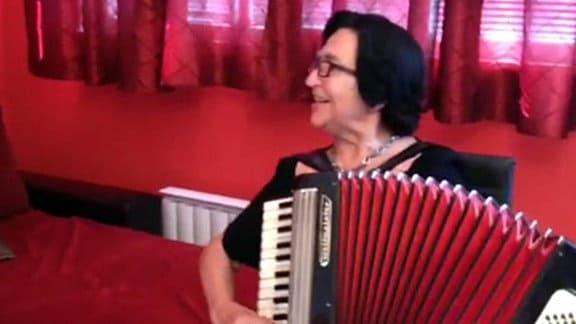 Ein Frau singt und spielt dabei Akkordeon.