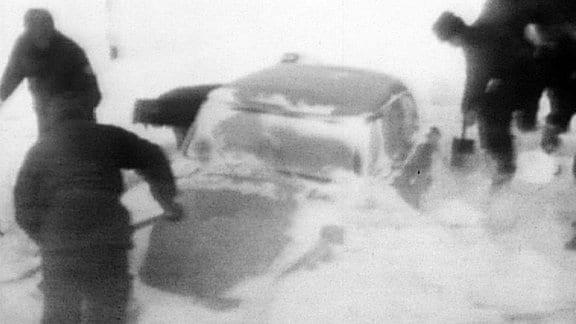 Ein eingeschneites Auto wird im Winter 1968 freigeschaufelt.