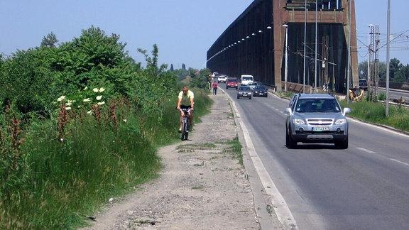 Ein Radfahrer fährt auf einem schotterigen, unbefestigten Seitenstreifen auf der Pancevo-Brücke in Belgrad.