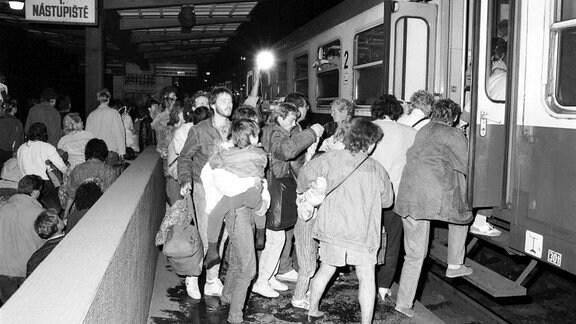 Ausreisewillige DDR-Bürger steigen Anfang Oktober 1989 auf dem Prager Bahnhof in einen bereitstehenden Zug, der sie in die Bundesrepublik bringen wird