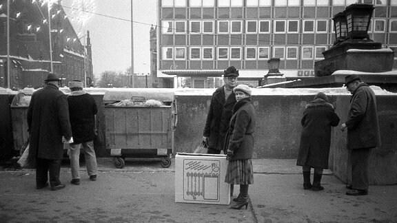 Männer und Frauen mit Weihnachtsgeschenken in den 80-er Jahren auf dem Leipziger Weihnachtsmarkt