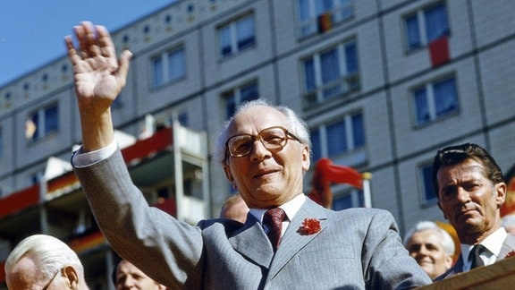 Der DDR-Partei- und Staatschef Erich Honecker winkt von einer Ehrentribühne in der Berliner Karl-Marx-Allee. (1986)
