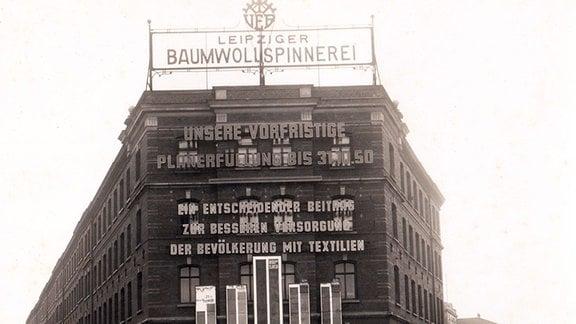 Die Front des VEB Leipziger Baumwollspinnerei - in Leipzig-Plagwitz mit einer großen Losung zur Planerfüllung.
