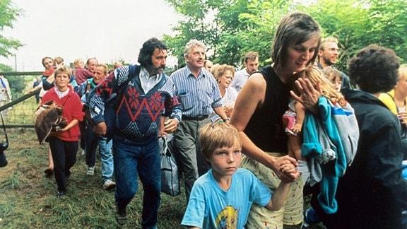 DDR-Flüchtlinge mit ihren Kindern gehen durch das geöffnete Grenztor