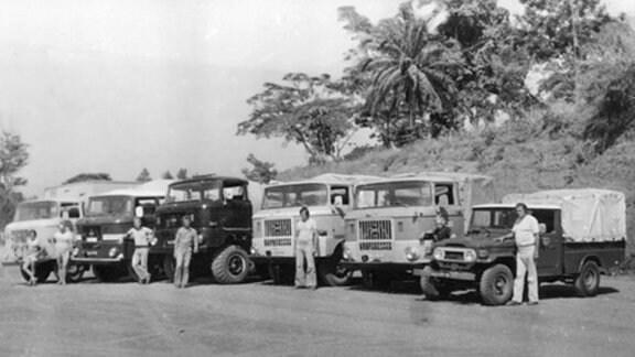 Eine Gruppe von Männern steht vor 6 Autos