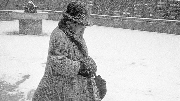 Alte Frau läuft mit Hut und Mantel mit viel Schnee von oben.