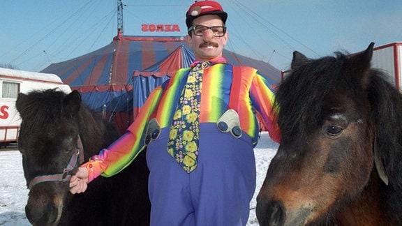 Clown Hoppi steht am 08.02.1996 mit zwei Ponys vor dem Zelt des Zirkus Aeros in Berlin Prenzlauer Berg. Während der Winterferien bietet der ehemalige Staatszirkus der DDR Kindern und Eltern ein buntes Programm mit zahlreichen Tierdressuren.