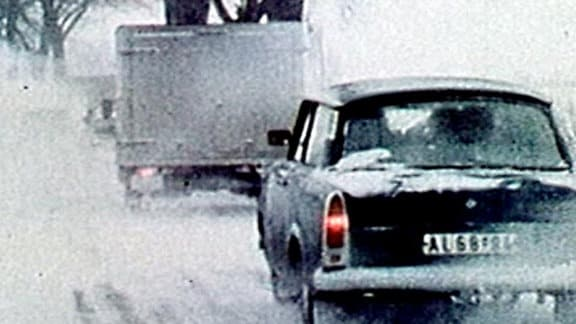 Ein dunkler Trabant fährt hinter einem Kleinlaster auf einer verschneiten Straße.