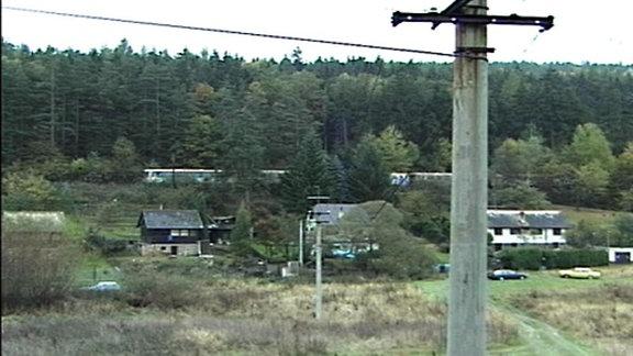 Blick auf eine Gartensiedlung mit Stromleitung im Vordergrund