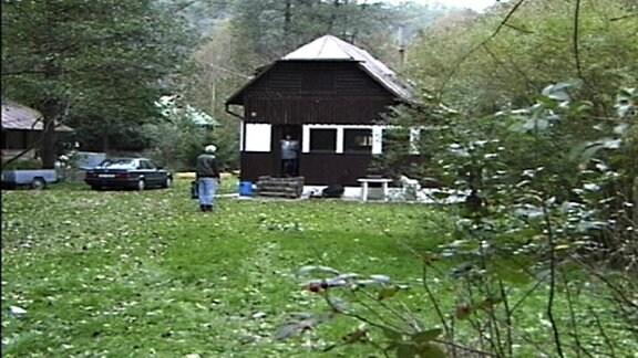 Ein Mann steht vor einem Gartenhaus auf einer großen Wiese