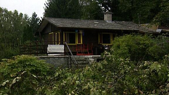 Gartenhaus mit gelb gestrichenen Fensterläden