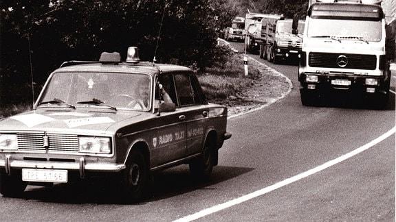 Tschechischer Polizei-Lada führt Lkw-Konvoi vom Grenzübergang Zinnwald hinunter Richtung Teplice an, Lkws dürfen Leitfahrzeug nicht überholen, Vermeidung von Unfällen talabwärts durch überhöhte Geschwindigkeit, Mitte der 1990er