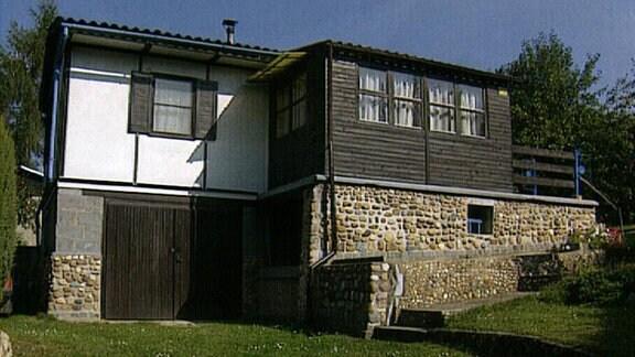 Goßes Holzhaus auf steinernem Unterbau in einem großen Garten.