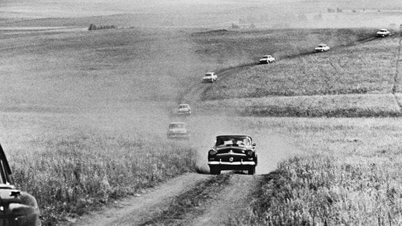 Autokolonne fährt auf gewundener Straße durch eine weite Feldlandschaft