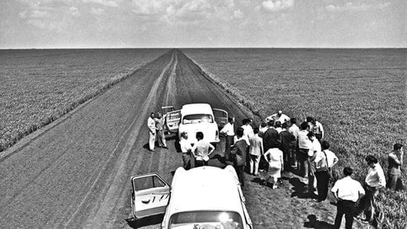 schnurgerade Straße in einem schier endlosen Feld. Zwei weiße Autos am unteren Bildrand, Frauen und Männer in Kostümen und Anzügen bestaunen die Weite der Landschaft
