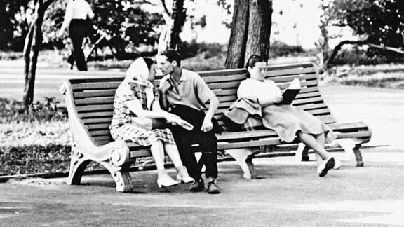 Drei Menschen auf einer Parkbank, links ein Pärchen,d ass zum kusse ansetzt, rechts daneben lesend, eine Frau mit langem Rock