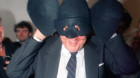 """Sichtlich amüsiert setzt der deutsche Bundesaußenminister Hans-Dietrich Genscher (FDP) eine mit übergroßen Ohren ausgestattete """"Genschman-Maske"""" auf. Die Maske wurde ihm am 23. September 1989 beim """"Tag der offenen Tür"""" vom """"Genschman-Fanclub"""" in der Bonner Villa Hammerschmidt übergeben."""