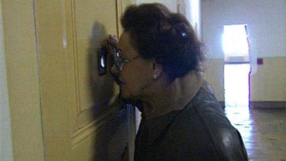 Eine Frau sieht durch einen Türspion.