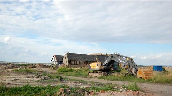 Zwei große Fachwerkhäuser auf einer Brachefläche, daneben ein großer Bagger.