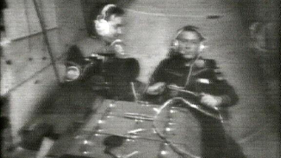 """Sigmund Jähn präsentiert die """"Multispektralkamera MKF 6"""", das Highlight der DDR-Raumfahrtentwicklungen. Das hochpräzise optische Instrument war vom VEB Carl Zeiss Jena 1975 entwickelt worden. Das Auflösungsvermögen der Multispektralkamera übertraf die damals besten Luftbildkameras um den Faktor 2,5. Aus 600 Kilometern Höhe waren noch Objekte von zehn Metern Größe erkennbar."""