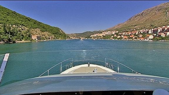 Blick über die Bugspitze eines Motorboots in eine Meeresbucht