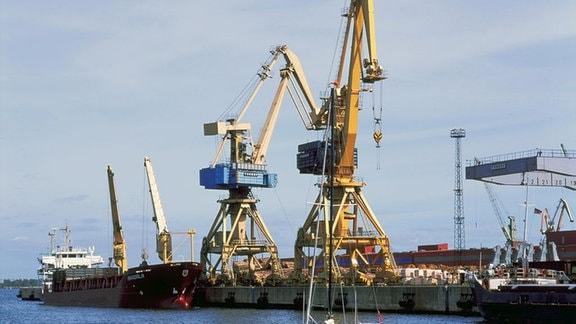 Blick vom Breitling auf Schiffe und Krane am Überseehafen von Rostock, aufgenommen im Sommer 1988.