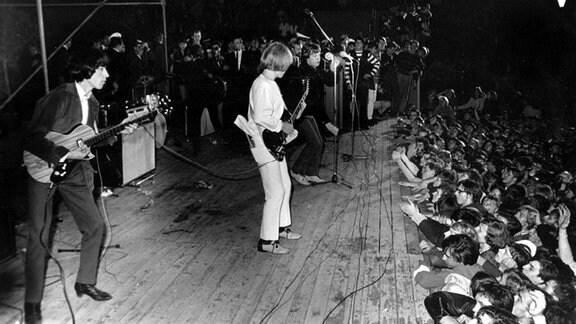 Die Rolling Stones 1965 auf der Waldbühne Berlin auf der Bühne seitlich aufgenommen - aus dem Publikum recken sich Hände auf die Bühne