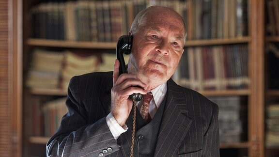 Prof. Schmitz (Otto Mellies) telefoniert mit dem russischen Generaloberst Burski um ihn vor einer möglichen Katastrophe im Bergwerk zu warnen. Doch Burski will nichts von der der Existenz eines unterirdischen Sees wissen, der zum Verhägnis für die Bergarbeiter werden könnte.