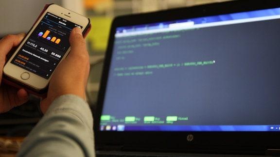 Ein Smartphone mit Balkendiagrammen auf dem Display wird vor einem Computer in den Händen gehalten