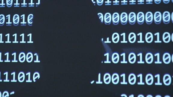 Dunkle Silhouette eines Menschen vor schwarzem Hintergrund mit weißen Zahlen, Null und Eins