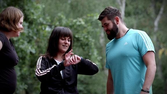 Zwei Frauen und ein Mann betrachten beim Sport ein Fitnessarmband