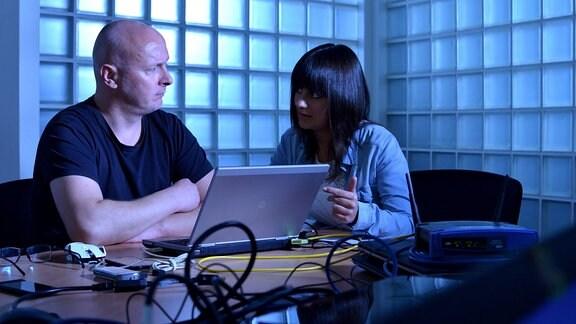 Ein Hacker und eine Reporterin des MDR sitzen vor einem Laptop und unterhalten sich.