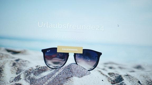Eine Sonnenbrille liegt am Strand
