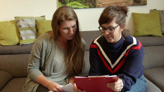 Zwei Frauen unterhalten sich auf einem Sofa sitzend.