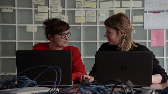 Zwei Frauen unterhalten sich am Arbeitsplatz.