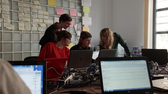 Vier Frauen besprechen sich am Arbeitsplatz.