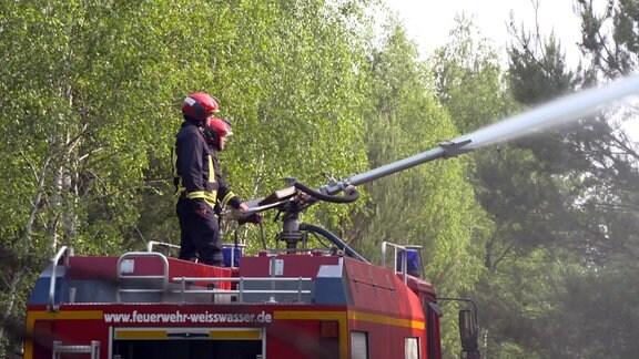 Feuerwehrleute spritzen Wasser