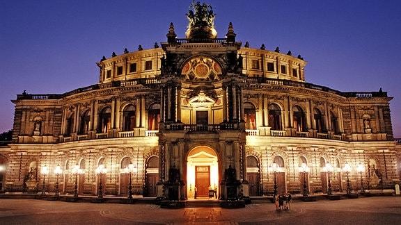 Nachtaufnahme der beleuchteten Fassade der Semperoper in Dresden