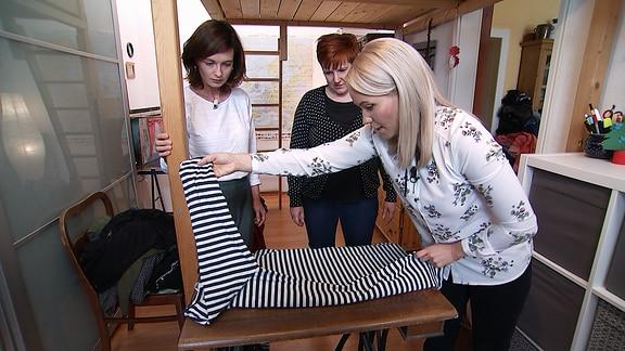 Janett Eger und zwei Frauen räumen einen Kleiderschrank auf.