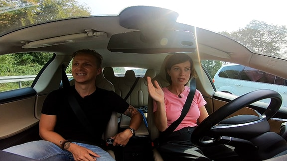 Janett Eger sitzt mit einem Mann in einem autonom fahrenden Auto. Sie hat die Hände vom Lenkrad genommen.
