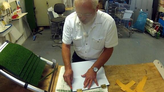Ein Mann schneidet Grasmatten zu.