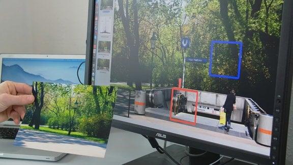 Eine Hand hält eine Aufnahme von einer Laterne in einem Park vor einen Monitor, auf dem ein Foto zu sehen ist, bei dem offenbar die Parkaufnahme hinter das Fotos eines U-Bahn-Eingangs montiert wurde. Eine rotes und ein blaues Quadrat markieren verdächtige Stellen.