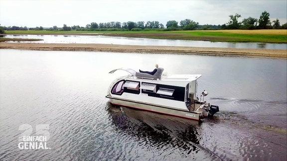 Ein Caravanboot fährt auf dem Wasser.