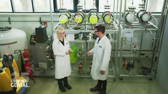 Zwei Menschen in Kitteln stehen vor einer Maschine.