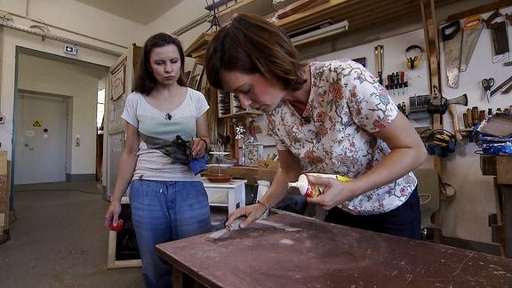 Janett Eger behandelt mit einer anderen Frau in einer Werkstatt eine alte Kommode.