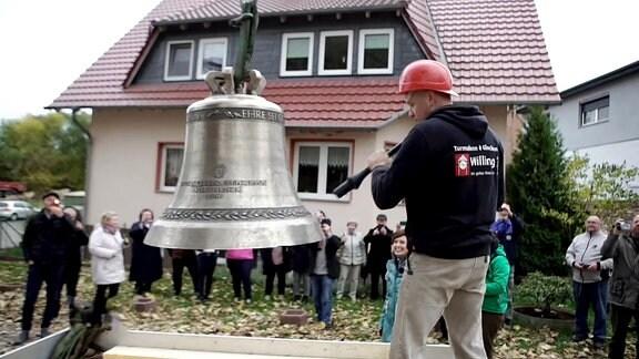 Uhrenrestaurator Steffen Willing schlägt die Glocke an