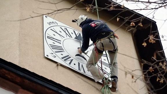 Uhrenrestaurator Steffen Willing beim Einsetzen des Zeigers in das Ziffernblatt der Turmuhr